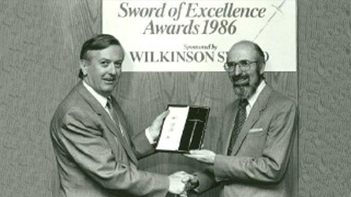 Peter Bateman (right) on behalf of the BPCA receives the Sword of Excellence from the Institute of Public Relations in 1986